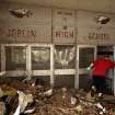 A woman makes her way into the damaged main entrance of Joplin High School Tuesday in Joplin, Mo. AP Photo