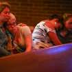 Annalyse Hurd, left, and Olivia Hutton, center, pray at the First Free Methodist Church after a shooting at Seattle Pacific University on Thursday, June 5, 2014. A man that shot students was disarmed by others at the scene. (AP Photo/seattlepi.com, Joshua Trujillo)