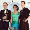 Tristan Chytroschek, left, Susanne Mertens, right, of Germany pose with presenter Prerna Wanvari after winning the Arts Programming award for