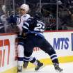 Tampa Bay Lightning's Sami Salo (6) is slammed into the boards by Winnipeg Jets' Chris Thorburn (22) during the second period of an NHL hockey game Tuesday, Jan. 7, 2014, in Winnipeg, Manitoba. (AP Photo/The Canadian Press, Trevor Hagan)