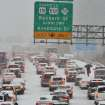 A motorist, right, who abandoned their vehicle, walks through stopped traffic on northbound Interstate 85 during a winter storm Wednesday, Feb. 12, 2014, in Durham, N.C. (AP Photo/The Charlotte Observer, Chuck Liddy) MAGS OUT; TV OUT; NEWSPAPER INTERNET ONLY
