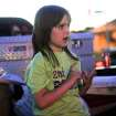 Addyson Roberts, 7, sits on the tailgate of her dad's truck and talks about her experience escaping the Plaza Towers Elementary school. Photo by KT King, The Oklahoman