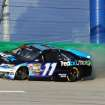 Denny Hamlin (11) hit the outside wall in between Turns 3 and 4 during the NASCAR Sprint Cup series auto race Saturday, June  28, 2014, at Kentucky Speedway in Sparta, Ky. The crash put him out of the race. (AP Photo/Garry Jones)