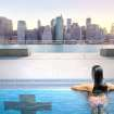 This artist's rendering provided by Plus Pool, Tuesday, April 22, 2014, shows a swimmer in the proposed floating pool which is to be positioned in New York's East River close to the Brooklyn shore. The pool, which is scheduled to open in 2016, would be the first of its kind because it's made of filtration material designed to make dirty river safe for swimming. The lower Manhattan skyline is in the background. (AP Photo/Plus Pool)