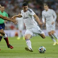 Photo - Real Madrid's James Rodriguez from Colombia duels for the ball with Atletico Madrid's Joao Miranda from Brazil, left, during a Spanish Super Cup soccer match at the Santiago Bernabeu stadium  in Madrid, Spain, Tuesday, Aug. 19, 2014 . (AP Photo/Daniel Ochoa de Olza)