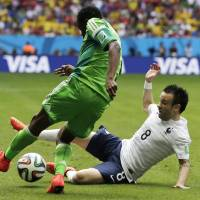 Photo - France's Mathieu Valbuena, right, slides in to kick the ball away from Nigeria's Ahmed Musa during the World Cup round of 16 soccer match between France and Nigeria at the Estadio Nacional in Brasilia, Brazil, Monday, June 30, 2014. (AP Photo/Petr David Josek)