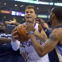 Photo - Los Angeles Clippers forward Blake Griffin, middle, drives between Memphis Grizzlies forward Zach Randolph, left, and Mike Conley during the first half of Game 2 of a first-round NBA basketball playoff series, Monday, April 22, 2013, in Los Angeles.  (AP Photo/Mark J. Terrill)