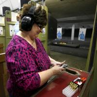 Photo - Peggy Osterholt of Okarche, Okla, gets ready to fire her handgun inside H&H Shooting Sports Complex in Oklahoma City, Tuesday, March 20, 2012. Photo by Bryan Terry, The Oklahoman