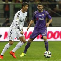 Photo - Real Madrid's Cristiano Ronaldo from Portugal, left, and Fiorentina's Borja Valero  challenge for the ball during their friendly soccer match  in Warsaw, Poland, Saturday, Aug. 16, 2014.(AP Photo/Czarek Sokolowski)