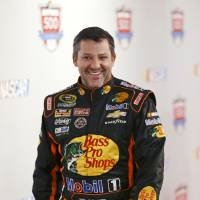 Photo - Driver Tony Stewart laughs as he moves from one interview station to another during NASCAR auto racing media day at Daytona International Speedway in Daytona Beach, Fla., Thursday, Feb. 13, 2014. (AP Photo/John Raoux)