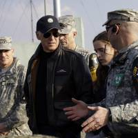 Photo - U.S. Vice President Joe Biden, center, is briefed by Lt. Col. Daniel Edwan, the commander of the JSA Security Battalion from Observation Post Ouellette during his tour of the Demilitarized Zone (DMZ), near the border village of Panmunjom, which has separated the two Koreas since the Korean War, South Korea, Saturday, Dec. 7, 2013. (AP Photo/Lee Jin-man, Pool)