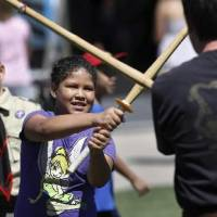Photo -  Samara Cranfield, 8, said she had fun jousting with a Kung Fu San Soo instructor at the tent sponsored by Phoenix Rising at Septemberfest 2012. Combatants used bamboo poles to test each other's skills. Cranfield attends Martin Luther King Jr. Elementary School in Oklahoma City. Photo by Jim Beckel, The Oklahoman Archive