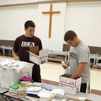 Photo - Lucas Gerdes, 15, (left) and Mac Wilsey arrange items in boxes as Edmond football players pack care packages to send to deployed military during a Blue Star Mother's event at the Peace Lutheran Church in Edmond, OK, Saturday, July 24, 2010. By Paul Hellstern, The Oklahoman