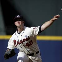 Photo - Atlanta Braves starting pitcher Alex Wood throws in the first inning of a baseball game against the Miami Marlins, Sunday, Aug. 31, 2014, in Atlanta. (AP Photo/David Goldman)