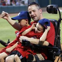 """Photo - Oklahoma City police officer Chad Peery acknowledges fans in August with sons McKade, 6, left, and Morgan, 4, on his lap as part of the """"Home Run for Life"""" promotion during a game between the Oklahoma City RedHawks and the Iowa Cubs at Chickasaw Bricktown Ballpark.   Photo by Nate Billings, The Oklahoman Archives"""