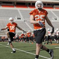 Photo - COLLEGE FOOTBALL: OSU's Josh Cooper (25) and Charlie Moore (18) warm up during the first spring football practice for the Oklahoma State University Cowboys, at Boone Pickens Stadium in Stillwater, Okla., Tuesday, March 9, 2010. Photo by Nate Billings, The Oklahoman ORG XMIT: KOD