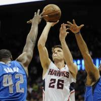 Photo - Atlanta Hawks forward Kyle Korver (26), shoots while defended by Dallas Mavericks  forward Elton Brand (42), and guard Vince Carter (25) during the first half of an NBA basketball game, Monday, March 18, 2013, in Atlanta. (John Amis/AP Photo)
