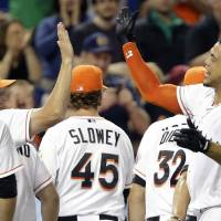 Photo - Miami Marlins' Giancarlo Stanton, right, high-fives manager Mike Redmond, left, after hitting a grand slam to defeat the Seattle Mariners 8-4 during the ninth inning of an interleague baseball game on Friday, April 18, 2014, in Miami. (AP Photo/Lynne Sladky)