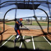 Photo - Houston Astros infielder Carlos Correa hits during a spring training baseball workout, Wednesday, Feb. 19, 2014, in Kissimmee, Fla. (AP Photo/Alex Brandon)