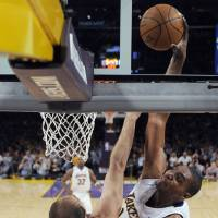 Photo - L.A. LAKERS / NBA PLAYOFFS: Los Angeles Lakers center Andrew Bynum, right, dunks over Oklahoma City Thunder center Nenad Krstic during the first half of an NBA basketball first-round playoff game in Los Angeles, Sunday, April 18, 2010. The Lakers won 87-79. (AP Photo/Chris Carlson) ORG XMIT: LAS205