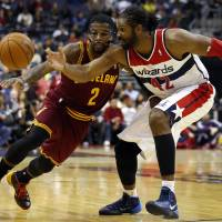 Photo - Washington Wizards forward Nene (42), from Brazil, slaps the ball away from Cleveland Cavaliers guard Kyrie Irving (2) in the first half of an NBA basketball game on Saturday, Nov. 16, 2013, in Washington. (AP Photo/Alex Brandon)