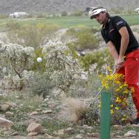 Photo - Victor Dubuisson, of France, hits out of the desert on the 20th hole in his championship match against Jason Day during the Match Play Championship golf tournament on Sunday, Feb. 23, 2014, in Marana, Ariz. (AP Photo/Ted S. Warren)