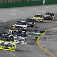 Photo - Pole-sitter Kyle Busch (51) leads the field into the second lap of the NASCAR Trucks auto race at Kentucky Speedway in Sparta, Ky., Thursday June 26, 2014. (AP Photo/Garry Jones)