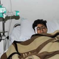 Photo - In this photo released by the Syrian official news agency SANA, an injured Syrian student, lies at a hospital bed after he was wounded when a mortar hit the al-Batiha school in al-Wafideen camp, about 25 kilometers (15 miles) northeast of Damascus, Syria, Tuesday Dec. 4, 2012. A mortar slammed into a ninth-grade classroom in the Damascus suburbs on Tuesday, killing 29 students and a teacher, according to state media, as the civil war closed in on President Bashar Assad's seat of power. (AP Photo/SANA)