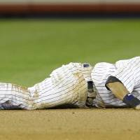 Photo -   New York Yankees shortstop Derek Jeter reacts after injuring himself in the 12th inning of Game 1 of the American League championship series against the Detroit Tigers early Sunday, Oct. 14, 2012, in New York.(AP Photo/Paul Sancya )