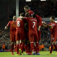 Photo - Liverpool's Daniel Sturridge is swamped by jubilant teammates including Jon Flanagan, top, after scoring against Sunderland during their English Premier League soccer match at Anfield Stadium, Liverpool, England, Wednesday March 26, 2014. (AP Photo/Jon Super)