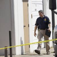 Photo -   An FBI agent enters Arc Electronics Inc. Wednesday, Oct. 3, 2012 in Houston. A Kazakhstan-born businessman was charged in the U.S. on Wednesday with being a secret Russian agent involved in a scheme to illegally export microelectronics from the United States to Russian military and intelligence agencies. (AP Photo/David J. Phillip)