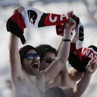 Photo - Canadian fans cheer during the men's ski slopestyle qualifying at the Rosa Khutor Extreme Park, at the 2014 Winter Olympics, Thursday, Feb. 13, 2014, in Krasnaya Polyana, Russia. (AP Photo/Andy Wong)