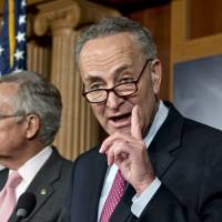 Photo - Sen. Charles Schumer, D-N.Y., right, accompanied by Senate Majority Leader Harry Reid of Nev., gestures during a news conference on Capitol Hill in Washington, Thursday, Nov. 29, 2012, after talks with Treasury Secretary Timothy Geithner on the fiscal cliff negotiations.  (AP Photo/J. Scott Applewhite)