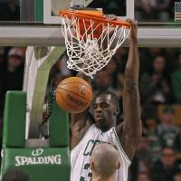Photo - Boston Celtics forward Brandon Bass, top, dunks against Washington Wizards center Marcin Gortat (4) during the first quarter of an NBA basketball game in Boston, Wednesday, April 16, 2014. (AP Photo/Elise Amendola)
