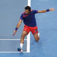 Photo - Jo-Wilfried Tsonga of France plays a backhand shot to Grzegorz Panfil of Poland during the men's final, Saturday, Jan. 4, 2014, at the Hopman Cup tennis tournament in Perth Australia. Tsonga won the match 6-3, 3-6, 6-3. (AP Photo/Theron Kirkman)