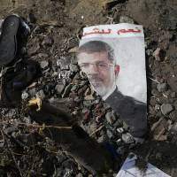 Photo - FILE - In this Friday, Aug. 16, 2013 file photo, a trampled poster of Egypt's ousted President Mohammed Morsi is seen on the ground outside the Rabaah al-Adawiya mosque, where supporters of Morsi had a protest camp in Nasr City, Cairo, Egypt. Arabic reads,