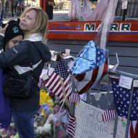 Photo - Holly Holland, right, of St. Louis, hugs her daughter Katie Holland while visiting a makeshift memorial in Boston, Monday, April 22, 2013. The memorial sits on Boylston Street, not far from where two bombs exploded near the finish line of the Boston Marathon, on Monday, April 15. (AP Photo/Steven Senne)