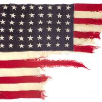 Photo - This photo provided by Bonhams shows a tattered 48-star American flag that flew aboard the U.S.-built LST 493 on D-Day that is being auctioned by Bonhams in New York on Thursday, June 5, 2014. The flag is among the hundreds of D-Day and other World War II artifacts being auctioned a day before the 70th anniversary of the history-changing invasion. The auction also features rare print-outs of the original series of hourly Dow Jones news bulletins with some of the first reports of the fighting on France's north coast on June 6, 1944. (AP Photo/Bonhams)