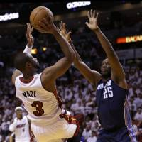 Photo - Miami Heat's Dwyane Wade (3) shoots over Charlotte Bobcats' Al Jefferson (25) during the first half in Game 1 of an opening-round NBA basketball playoff series, Sunday, April 20, 2014, in Miami. (AP Photo/Lynne Sladky)