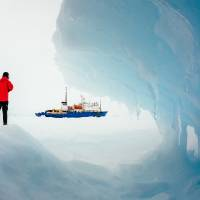 Photo - In this Tuesday, Dec. 31, 2013 image provided by Australasian Antarctic Expedition/Footloose Fotography, passengers from the Russian ship MV Akademik Shokalskiy trapped in the ice 1,500 nautical miles south of Hobart, Australia, walk around the ice. Passengers on board a research ship that has been trapped in Antarctic ice for a week are expected to be rescued by helicopter, after three icebreakers failed to reach the paralyzed vessel, officials said Tuesday.  (AP Photo/Australasian Antarctic Expedition/Footloose Fotography, Andrew Peacock) EDITORIAL USE ONLY