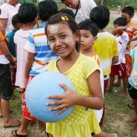 Photo - In this November 2013 photo provided by the One World Futbol Project, a school girl holds a blue One World Futbol at a school in Mawlamyine, Myanmar. The ball was part of a larger donation of 5,000 plus balls to the country. When Lisa Tarver and husband Tim Jahnigen set out four years ago to distribute their indestructible blue soccer balls to areas in need across the world, little did they know how far the project would evolve in just four years, in the span of a single World Cup cycle. Their One World Futbol project has shipped more than 850,000 soccer balls to organizations worldwide, touching the lives of some 30,000,000 children, many of whom would never have had access to such equipment or would have come up with their own version of a ball. (AP Photo/One World Futbol Project)