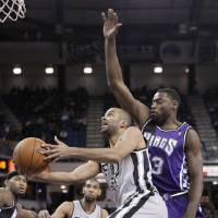 Photo - San Antonio Spurs guard Tony Parker, of  France, drives to the basket past  Sacramento Kings guard Tyreke Evans, right, during the first quarter of an NBA basketball game in Sacramento, Calif., Tuesday, Feb. 19, 2013. (AP Photo/Rich Pedroncelli)
