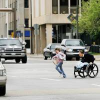 Photo - A woman in a wheelchair and children hurry to cross Hudson Avenue between the County Courthouse and City Hall in this 2009 photo. The street has since been narrowed from six to four lanes and converted from one-way to two-way traffic. Photo by Jim Beckel, The Oklahoman Archives