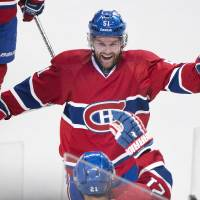 Photo - Montreal Canadiens' Brian Gionta, foreground, celebrates with teammate David Desharnais (51) after scoring the winning goal against the New York Rangers during overtime of an NHL hockey game, Saturday, April 12, 2014, in Montreal. Montreal won 1-0. (AP Photo/The Canadian Press, Graham Hughes)