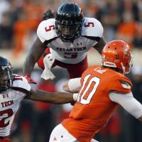 Photo - OSU: Oklahoma State's Clint Chelf (10) avoids the pressure of Texas Tech's D.J. Johnson (12) and Tre' Porter (5) during a college football game between Oklahoma State University and the Texas Tech University (TTU) at Boone Pickens Stadium in Stillwater, Okla., Saturday, Nov. 17, 2012. Photo by Sarah Phipps, The Oklahoman