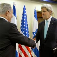 Photo - U.S. Secretary of State John Kerry, right, shakes hands with Israeli Prime Minister Benjamin Netanyahu in Jerusalem, Monday, March 31, 2014, for a previously unannounced stop in Israel to continue working on talks about the Middle East peace process. (AP Photo/Jacquelyn Martin, Pool)