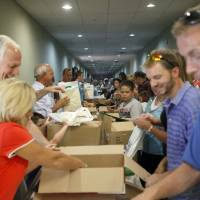 Photo - Members of Capitol Hill Baptist Church pack school supplies in preparation for the church's 2010 Back-to-School Bash.  SARAH PHIPPS - THE OKLAHOMAN