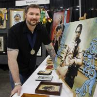 Photo - Artist Dylan Cavin, of Norman, is shown with some of his art at his booth at the Red Earth Native American Cultural Festival in the Cox Convention Center.  The artwork at right,   titled,
