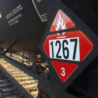 Photo - FILE - This Nov. 6, 2013 file photo shows a warning placard on a tank car carrying crude oil near a loading terminal in Trenton, N.D. Thousands of older rail tank cars that carry crude oil would be phased out within two years under regulations proposed in response to a series of fiery train crashes over the past year. Transportation Secretary Anthony Foxx said the government's testing of crude oil from the Bakken region of North Dakota and Montana shows the oil is on the high end of a range of volatility compared with other crude oils, meaning it's more likely to ignite if spilled. (AP Photo/Matthew Brown, File)