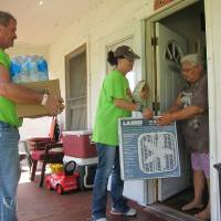 Photo -  Jesus House residents Richard Williams, 48, and Leslie Stickney, 42, give a box fan to a resident of the Orchard Park neighborhood during a recent Adopt-A-Block outing. Photo by Carla Hinton, The Oklahoman
